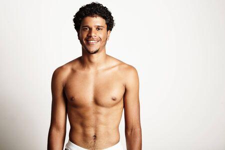 junger lächelnder Mann topless auf einer weißen Wand