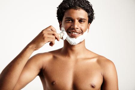 ypung Mann setzt Schaum für Rasur auf Gesicht LANG_EVOIMAGES
