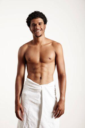 junger Mann im weißen Tuch auf einem weißen Hintergrund