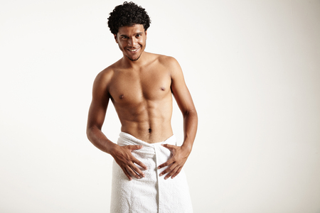 sauna nackt: junge Latin Mann im weißen Tuch lächelt
