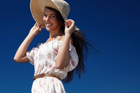 blowed: woman catched summer hat blowed by wind wears floral dress LANG_EVOIMAGES