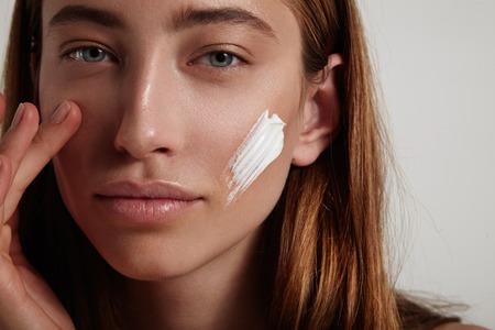 femme de toucher sa peau de visage avec la crème sur une autre joue