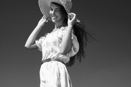 blowed: bw portrait of woman catched summer hat blowed by wind wears floral dress
