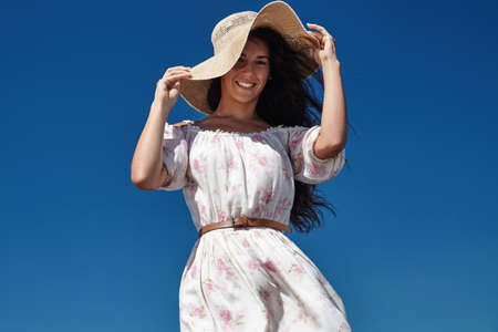 blowed: woman catched summer hat blowed by wind