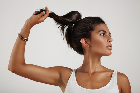 femenine: spanish woman holding and pull a ponytail