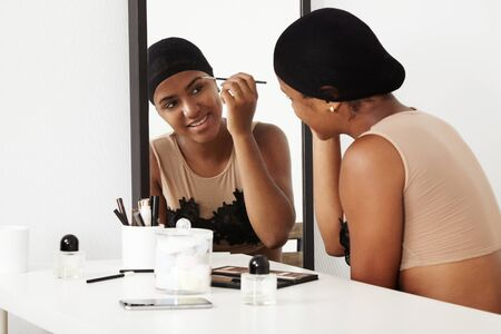 daily routine: black woman makeup her face in mirror. daily routine LANG_EVOIMAGES