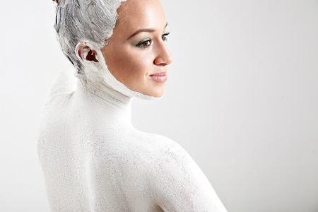 clarifying: woman with a white clay from the back. body treatment§