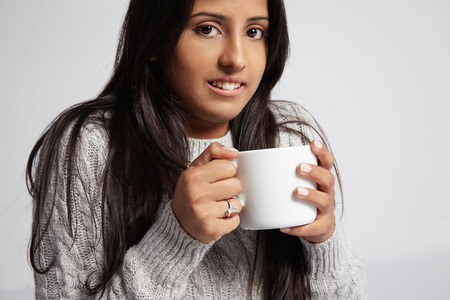 freezed: freezed woman drinks hot tee wears knitted sweater