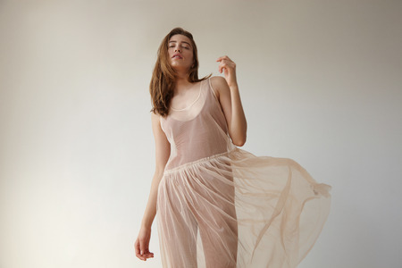 transparent dress: pretty delicate woman with flying transparent dress in loft studio LANG_EVOIMAGES