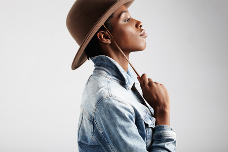 femenine: black womans profile wears jeans jacket and hat