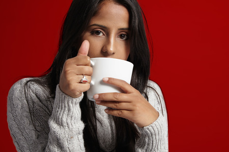 woman with brunette straight hair drinks hot coffe at cold time Stock Photo