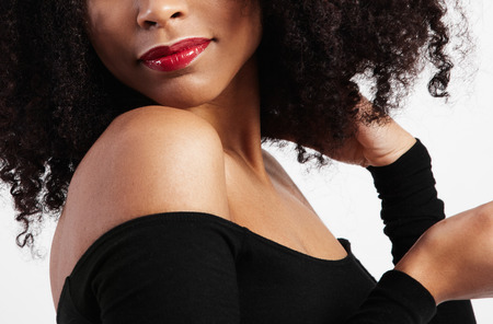femenine: closeup of black woman lips with glossy red lipstick