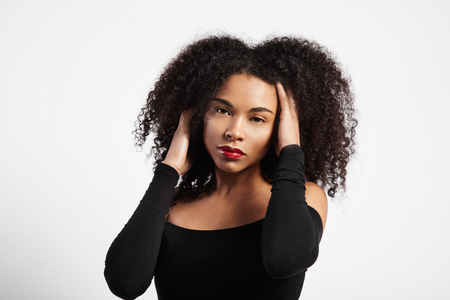 femenine: black woman with ideal skin touching her black curly hair