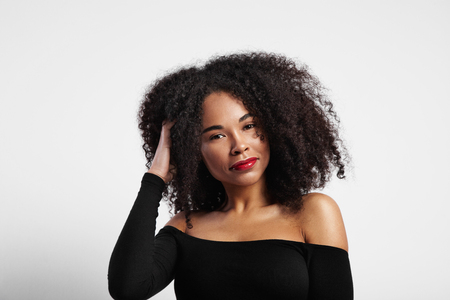 femenine: woman touches her curly afro hair LANG_EVOIMAGES
