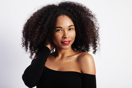 pretty black woman: pretty black woman touches her curly hair LANG_EVOIMAGES