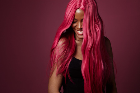 mixed race black woman with pink hair happy smiling. creative hair colour Standard-Bild