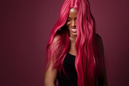 Razza mista donna nera con i capelli rosa sorridente felice. colore dei capelli creativo Archivio Fotografico - 73309234