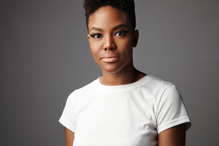 hait: portrait of black woman with short haircut with drama makeup eyes in grey background