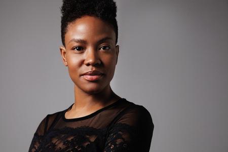 hait: black woman watching at camera, short haircut ideal skin