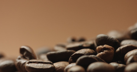 freshly roasted coffee beans isolated on brown. studio shoot