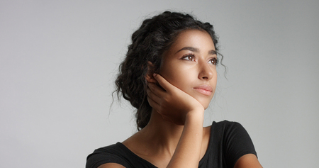 Attractive young Middle Eastern model touching her pretty face with flawless skin and smiling Archivio Fotografico