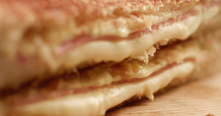 closeup of handmade delicious sandwich with ham and cheese. cutting it and press to show cheese texture. breackfast sandwich Stock Photo