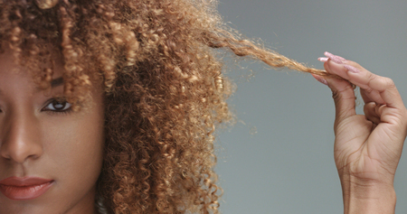mixed race black woman with neutral makeup portrait. Curly hair ideal skin, studio, grey background