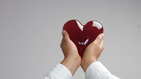 jelly-like red heart in mans hand holding it gently