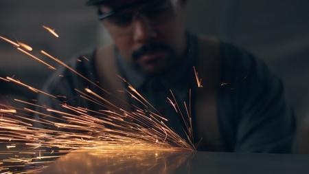 Worker using industrial grinder. Worker in garage makes work with metall and grinder. flying sparks worker in blur, sparks in focus