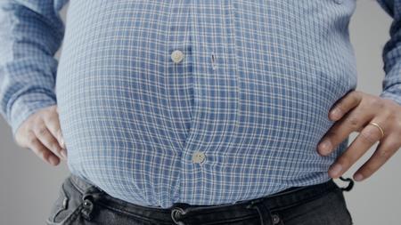 L'homme en surpoids en shrt est petit pour lui avec un énorme ventre et des boutons ouverts Banque d'images