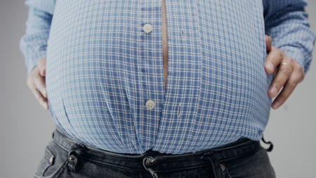 Overweight man in shrt is small to him with huge belly and open buttons