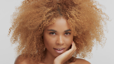 mixed race black blonde model with curly hair chin down watching to the camera Stockfoto