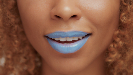 mixed race black blonde model with curly hair closeup of mouth painted with bright blue lipstick smile