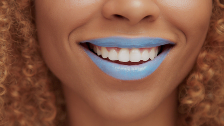 mixed race black blonde model with curly hair closeup of mouth painted with bright blue lipstick laughing mouth