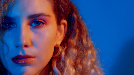 half of a face of model in blue-red coloured light