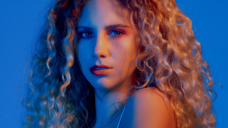 serious gorgeous woman with huge curly blond hair. Coloured light portrait