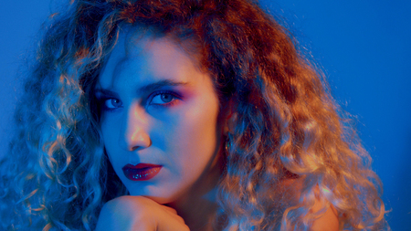 closeup portrait of blonde woman in blue-red light Stockfoto