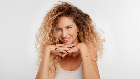 head and shoulders plan of blonde wooman with big curly hair in studio on white put chin on two crossed hands
