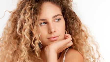 closeup portraitof green eyed model with big curly blonde hair, ideal skin. Watching aside with chin on hand Stockfoto