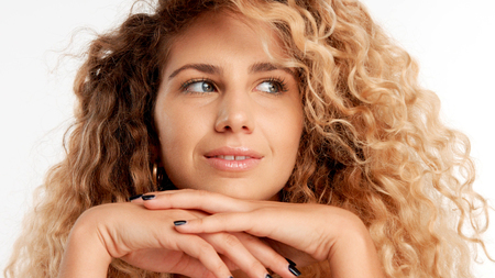 closeup portraitof green eyed model with big curly blonde hair, ideal skin with head on her hands watching aside