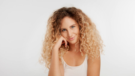 head and shoulders plan of blonde wooman with big curly hair in studio on white watching to the camera