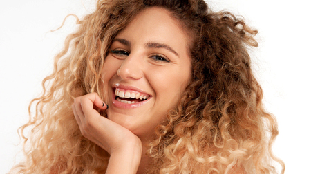 closeup portraitof green eyed model with big curly blonde hair, ideal skin and laughing