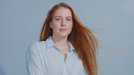 Ginger head red hair, ginger hair model with blue big eyes in studio with blowing hair on blue background. Beauty straight shiny hair blowing,