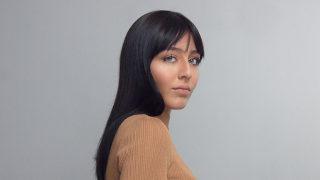 frontal portrait of mixed race eastern model brunette turned her face to the camera. and smiling slightly Stockfoto