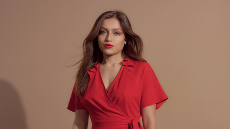 woman in red dress on beige background looking to the camera, dating look Red lips Stockfoto