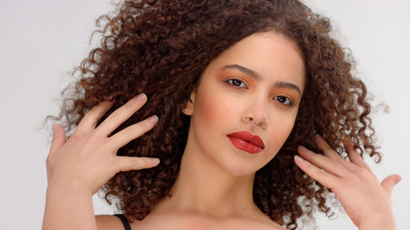hair blowing closeup portrait of mixed race model with freckles touches her hair Stockfoto