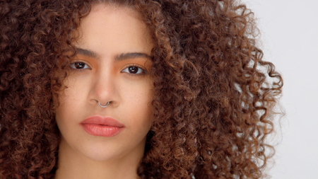 hair blowing closeup portrait of mixed race model with freckles watching to the camera directly