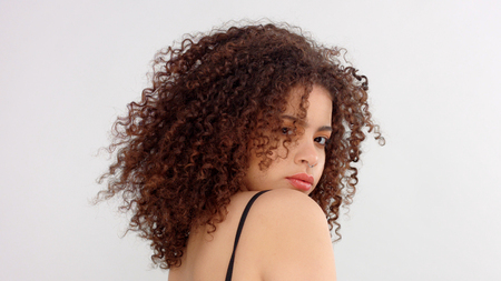 hair blowing closeup portrait of mixed race model with freckles backside shood and model turned her face to the camera Stockfoto
