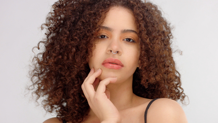 hair blowing closeup portrait of mixed race model with freckles touches her skin Stockfoto