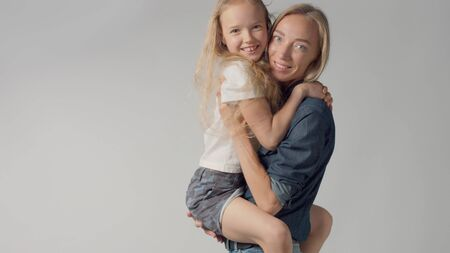 Mother with her teen daughter on hands in studio watching to the camera and smiling Foto de archivo - 133517122
